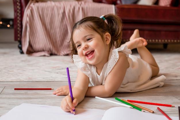 幸せな少女は家の床にあり、色鉛筆で描きます。子供の発達。家にいる