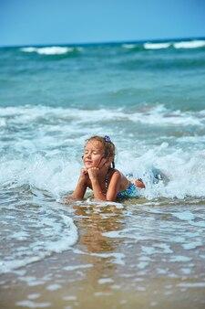 幸せな少女は波の海岸にあります。