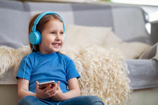 Счастливая маленькая девочка слушая музыку в голубых наушниках, дома
