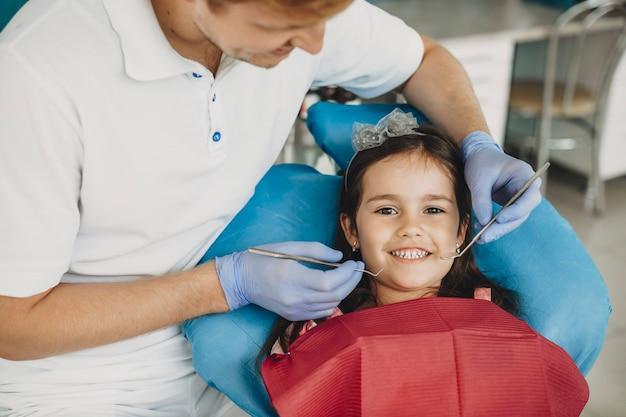 小児歯科医による歯の検査を行った後、カメラを見ている幸せな少女。