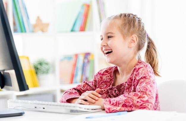 Счастливая маленькая девочка, глядя на экран компьютера, сидя за столом в классе