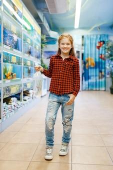 애완 동물 상점에서 금붕어를 찾고 행복 한 어린 소녀