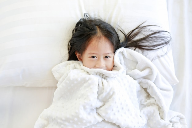 Happy little girl lying on bed with blanket and looking at camera. top view.