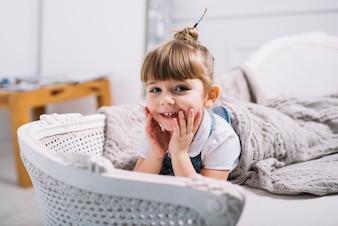 Happy little girl lying on sofa under blanket