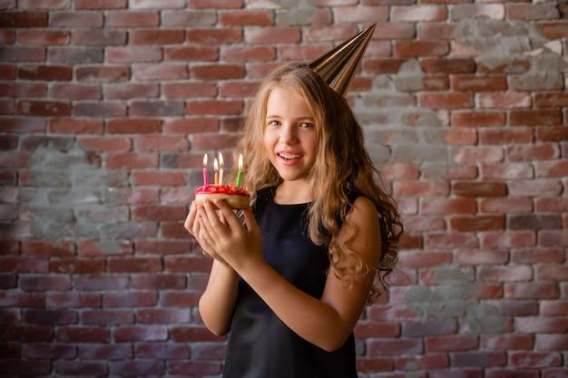 幸せな少女は願い事をし、誕生日にケーキにろうそくを吹き消します