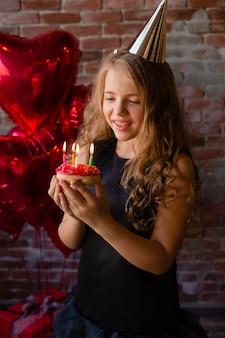 幸せな少女は願い事をし、ケーキにろうそくを吹き消します