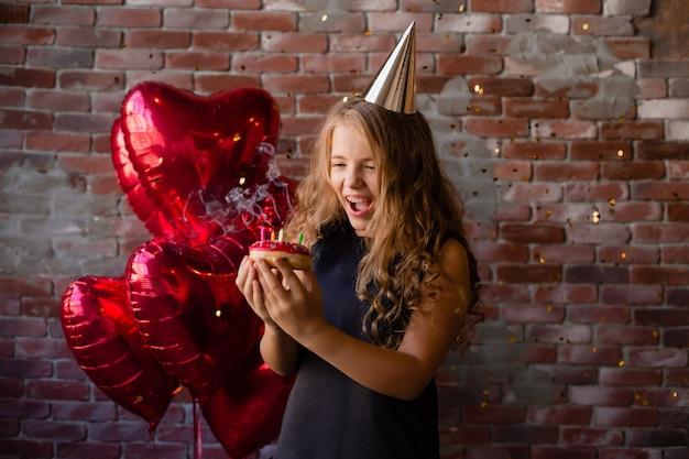 행복 한 어린 소녀는 소원을 만들고 케이크에 촛불을 불어