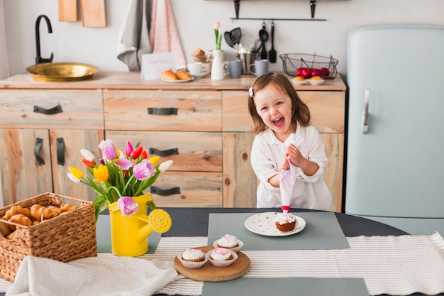 Happy little girl making cupcake