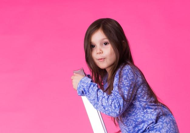 ピンクの壁の上の折りたたみはしごで幸せな少女。