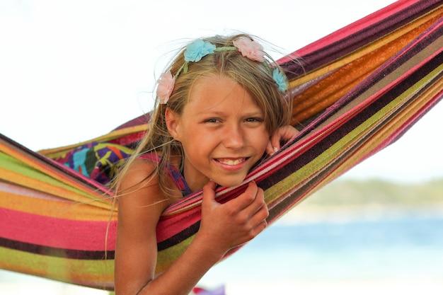 海の近くのハンモックで幸せな少女