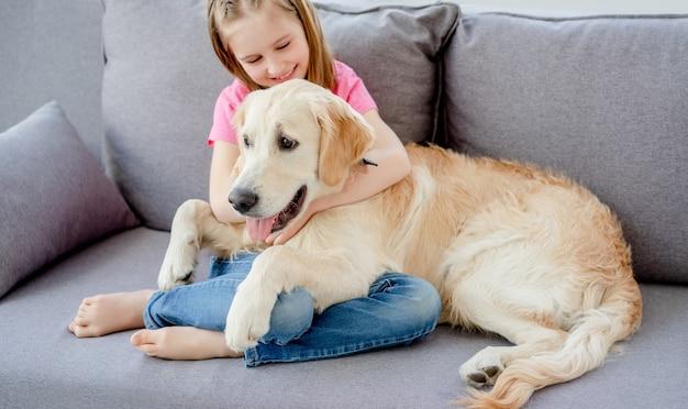 Счастливая маленькая девочка на диване с золотистым ретривером в светлой комнате