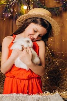 농장에서 행복한 어린 소녀는 건초 배경에 그녀의 팔에 흰 토끼를 안고