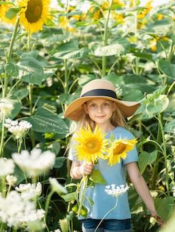 夏のひまわり畑で幸せな少女。