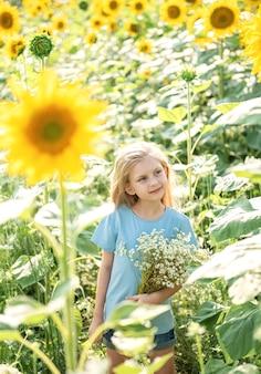 Счастливая маленькая девочка на поле подсолнухов летом.