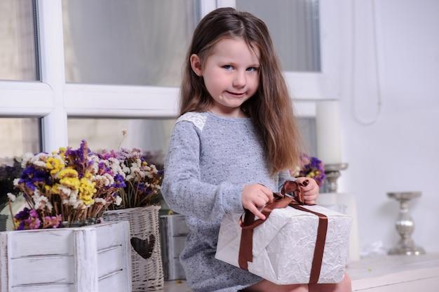 Счастливая маленькая девочка, открывая настоящую коробку.