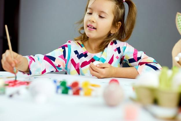 家でブラシの卵で描く幸せな少女の絵。イースターの準備をし、楽しんで、ごちそうを祝う子供。ハッピーイースター、diy