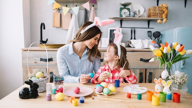 Happy little girl painting eggs for easter with mother