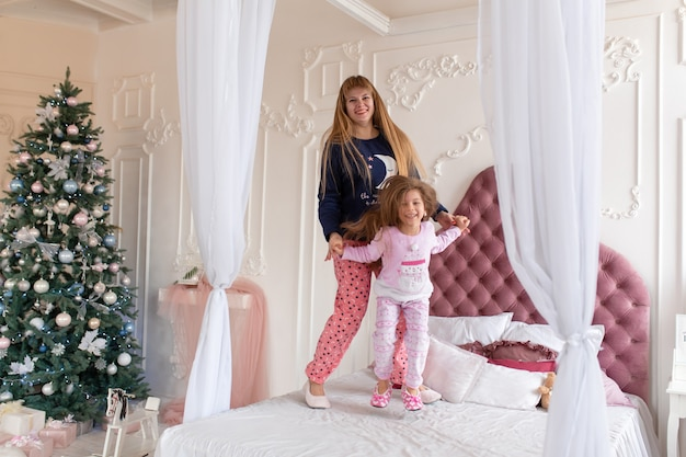 Happy little girl in pajamas is jumping with mom on the bed