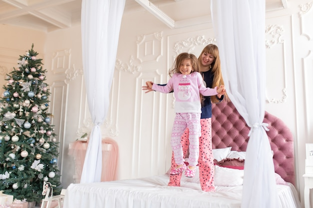 Happy little girl in pajamas is jumping with mom on the bed.