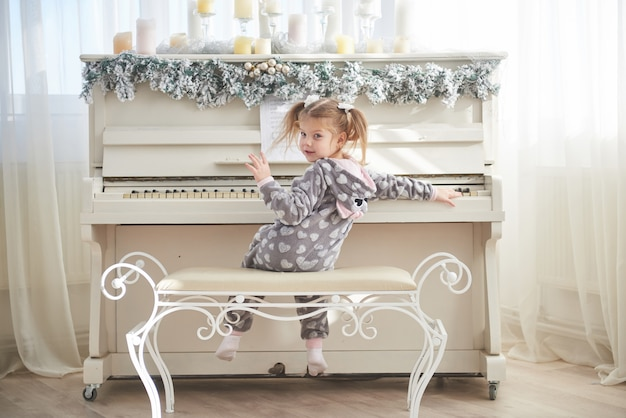 Happy little girl play the piano on christmas day