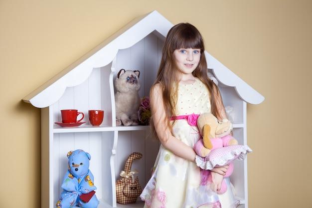 Счастливая маленькая девочка играет с игрушками в своей комнате