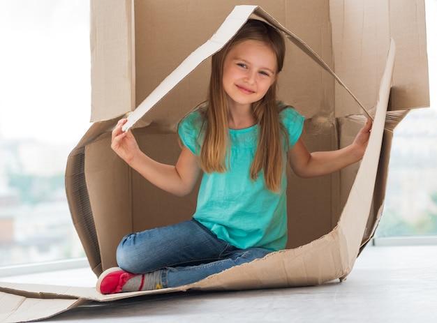 それを彼女の家にする段ボール箱で遊んで幸せな少女