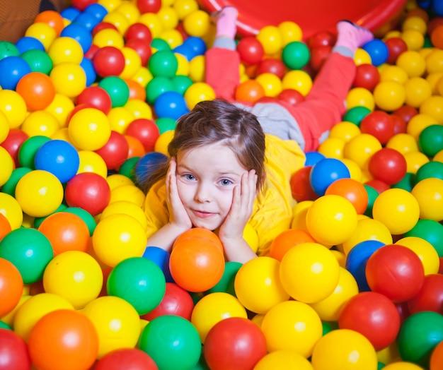 Счастливый маленькая девочка, играя в красочных шаров. счастливый ребенок, играющий на красочные пластиковые шарики в игровом центре