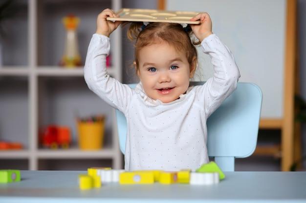 Счастливая маленькая девочка, играя, сидя за столом