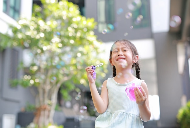 Happy little girl playing soap bubbles in garden.