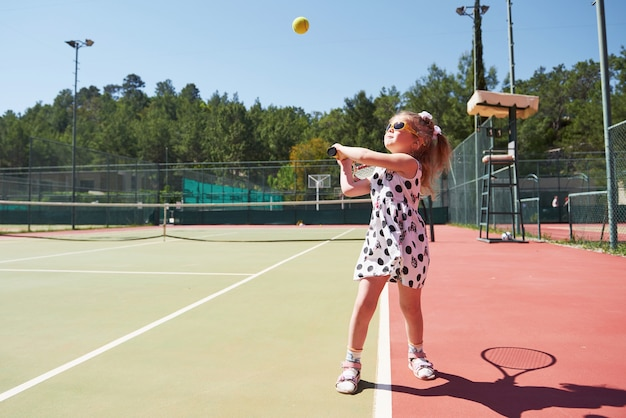 Happy little girl playing tennis. summer sport