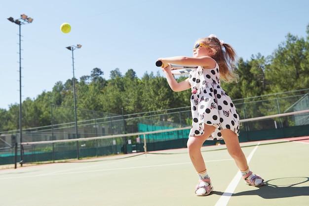 Счастливая маленькая девочка, играя в теннис. летний спорт