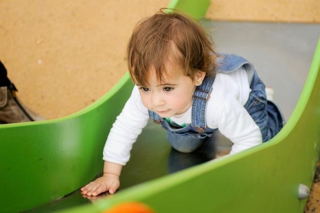 Bambina felice che gioca in un parco giochi urbano.
