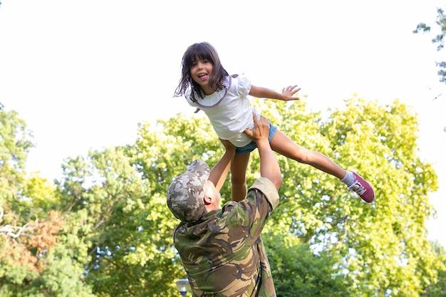 Bambina felice che gioca con il papà in uniforme militare. vista posteriore del padre che solleva sua figlia.