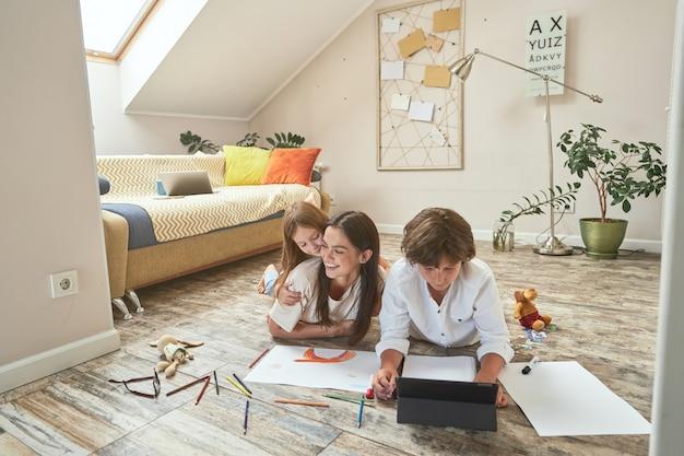 でリビングルームの床に横たわっている間、母親と遊んで楽しんでいる幸せな少女