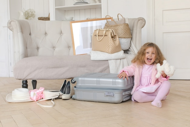 Happy little girl playing with a retro suitcase