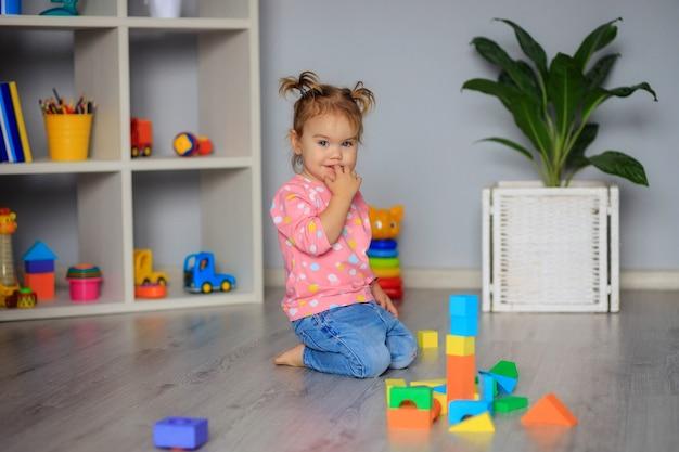 Счастливая маленькая девочка, играя с игрушками дома, в детском саду или ясли. развитие ребенка.