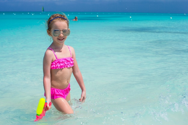Happy little girl playing with toys during caribbean vacation