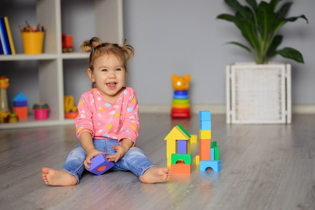 Happy little girl playing with toys at home, in kindergarten or nursery. development of the child.