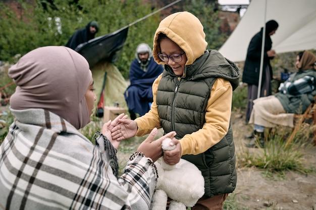 ヒジャーブで若い女性と遊ぶ幸せな少女