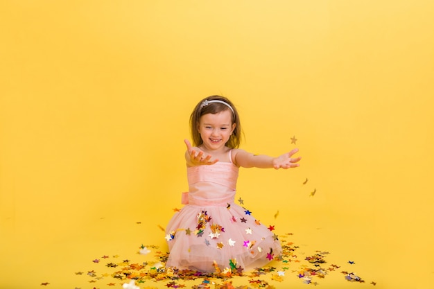 Happy little girl in a puffy pink dress catches confetti with her hands on a yellow isolated