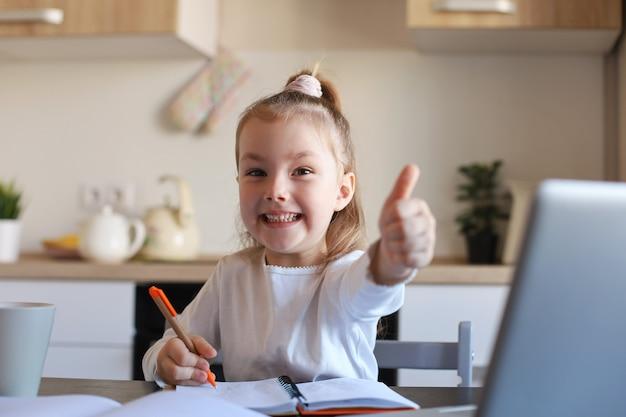 幸せな小さな女の子の生徒は、自宅でラップトップを使用してオンラインで勉強し、小さな子供を笑顔で親指を立ててクラスやレッスンをお勧めします。