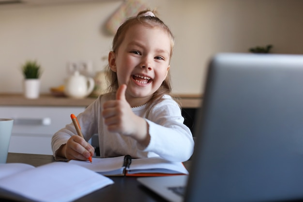Happy little girl pupil study online using laptop at home, smiling small child show thumb up recommend class or lesson.