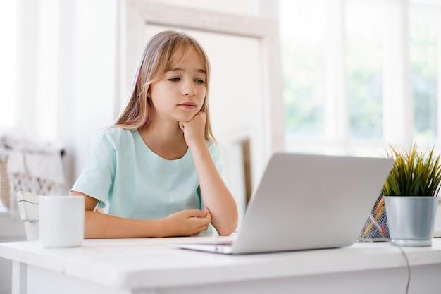 집에서 노트북을 사용하는 행복한 어린 소녀 학생