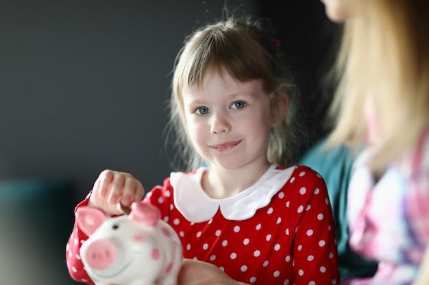 Счастливая маленькая девочка кладет монеты в копилку
