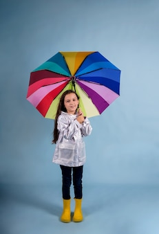 A happy little girl in a raincoat and rubber boots stands and holds a multi-colored umbrella on a blue background with a copy of the space