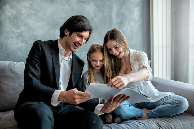 Счастливая маленькая девочка читает книгу с родителями дома