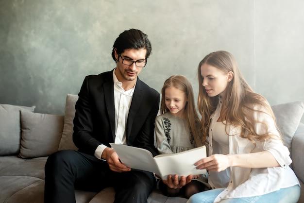 행복 한 어린 소녀 집에서 그녀의 부모와 함께 책을 읽고