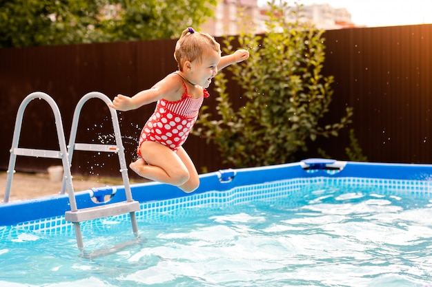 Happy little girl in red swimsuit jumping into outdoor swimming pool at home. baby girl learning to swim. water fun for children.