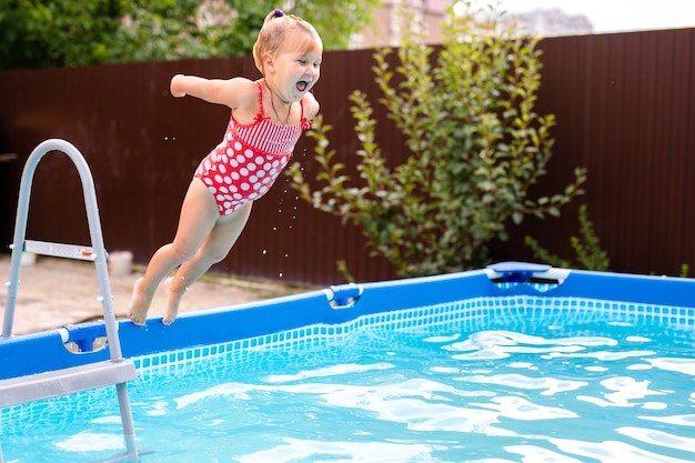 Happy little girl in red swimsuit jumping into outdoor swimming pool at home.