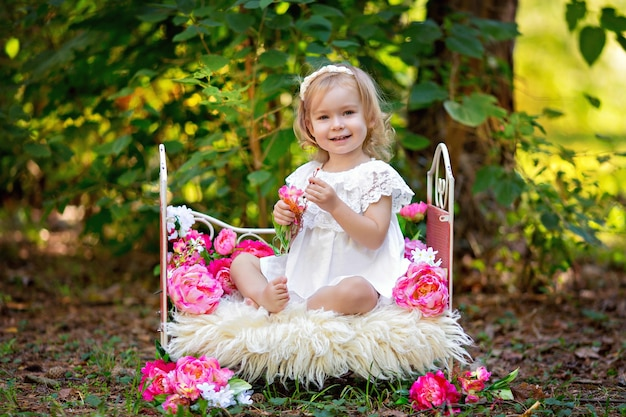Happy little girl in retro princess outfit in bed with pink flowers outdoors in summer